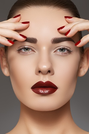 red lip: Luxury fashion style, manicure, cosmetics and make-up. Dark lips makeup & nails polish. Close-up portrait of female model with red lipstick, fingernails and clean skin