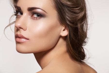 Glamour portret van mooie vrouw model met dagverse make-up en romantische golvend kapsel. Fashion glanzende highlighter op de huid, sexy glans lippen make-up en donkere wenkbrauwen