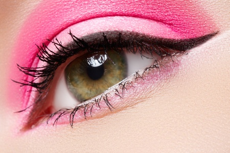 Cosmetics and beauty care. Macro close-up of beautiful green female eye with bright fashion runway make-up. Pink eyeshadows and black eyeliner  photo