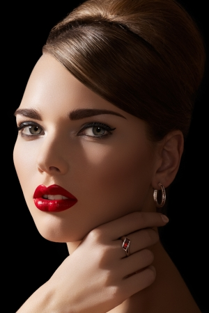Beautiful woman model with retro hairstyle and bright make-up. Accessories, jewelry gold ring and earrings with ruby. Alluring vintage romantic style, chic makeup and luxury jewellery