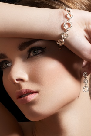 bracelet: Beautiful woman model in retro style make-up. Accessories, jewelry gold bracelet and earrings with diamonds. Chic makeup and luxury jewellery  Stock Photo
