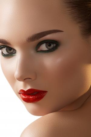 cejas: Close-up retrato de la cara de la pureza hermosa mujer con maquillaje brillante los labios de color rojo y color verde oscuro, ojos ahumados de maquillaje. Sexy modelo con la piel limpia y brillante