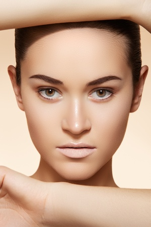 ageing: Portrait of sexy caucasian young woman. Natural spa beauty with pure skin. Beautiful model with natural make-up, clean skin on beige background