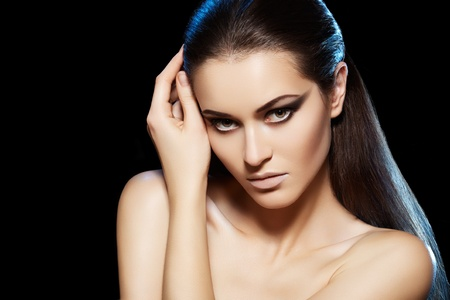 Beautiful sexy woman model with dark evening fashion make-up, brunette straight hairstyle in blue light on black background