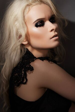 Beautiful blond woman model in chic lacy black dress, with dark punk rock gloss make-up. Evening and night style  Stock Photo - 11713957