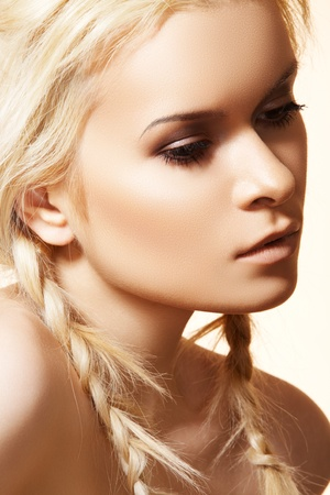 Beautiful blond woman with fashion hairstyle with braids. Hippie style. Portrait of glamour model