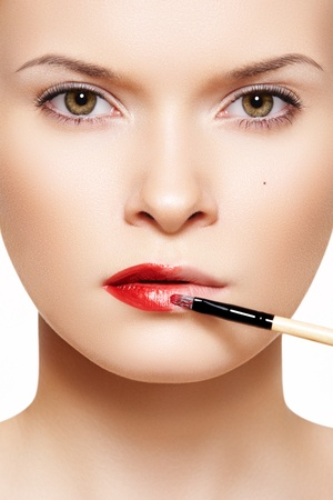 Close-up frontal portrait of beautiful woman model applying lipstick using lip concealer brush  photo