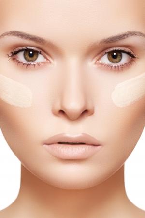 tratamiento facial: Maquillaje y cosmética. Primer retrato de la cara hermosa modelo de la mujer con la fundación de la piel en el fondo blanco Foto de archivo