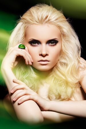 Alluring blond woman model with big ring in magic green mist. Glamour and fashion style. Real lights effect: mixed light with long exposure.  photo