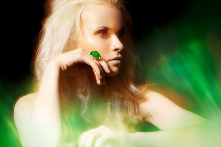 magic eye: Luxury blond woman model with fashion dark make-up, glamour volume curly hair, chic jewelry. Accessories. Platinum ring with big green jewel. Real lights effect: mixed light with long exposure  Stock Photo