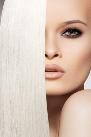 Sensual woman model with shiny straight long blond hair and chic evening make-up. Health, beauty, wellness, haircare, cosmetics and make-up. Beautiful fashion platinum hairstyle  Foto de archivo