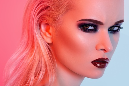 Punk rock style or halloween make-up. Fashion woman model face with bright glamour makeup. Perfect skin, black gloss eyeshadows on eyes and dark brown glossy lips visage. Portrait in red light  photo