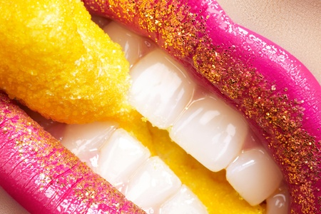 Sweet womans smile with beautiful bright fashion make-up, gold glitter on lips, white health teeth and holiday yellow candy  photo