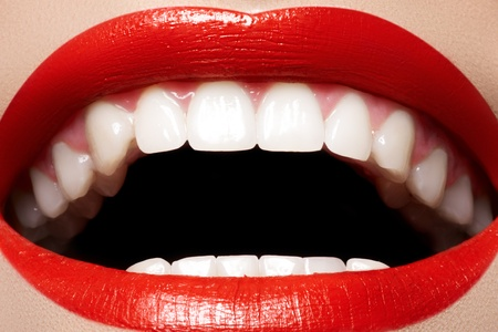 mouth close up: Close-up happy female smile with healthy white teeth, bright red gloss lips make-up. Cosmetology, dentistry and beauty care. Macro of womans smiling mouth  Stock Photo