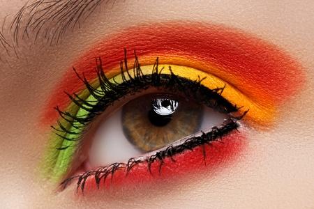 Cosmetics and beauty care. Macro close-up of beautiful green female eye with bright fashion runway make-up. Rainbow eyeshadows and black eyeliner