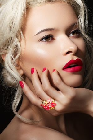 Wellness, cosmetics and romantic retro style. Close-up portrait of sensuality beautiful blond woman model face with fashion make-up, sexy evening red lips makeup and bright red manicure  Stock Photo