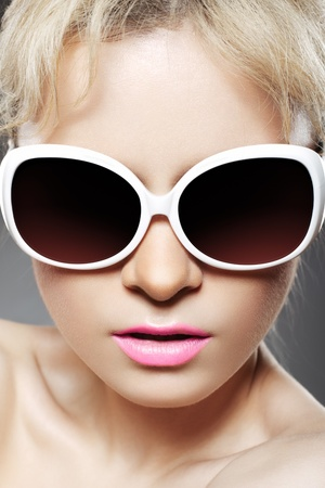 Glamour portrait of beautiful young woman model in big fashion white sunglasses with pink lip make-up  photo