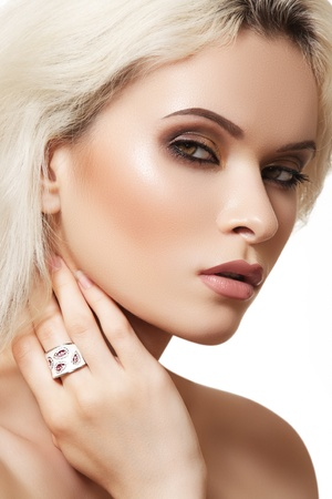 Beautiful blonde woman model with brown smoky-eye make-up and white ring on white background. Elegance style  photo
