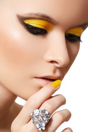 Close-up portrait of beautiful model face with neon bright yellow fashion make-up and with big crystal ring  photo