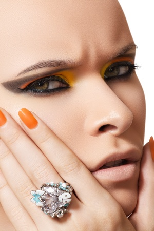 Accessories, big crystal ring. Model with facial emotion and neon bright yellow fashion make-up  photo