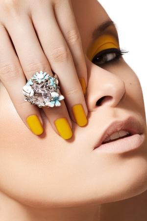 modellini: Close-up ritratto del volto di bel modello con neon giallo moda make-up e con l'anello grosso cristallo. Disco trucco e manicure, luminoso smalto