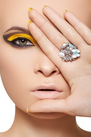 Close-up portrait of beautiful model face with neon bright yellow fashion make-up and with big crystal ring