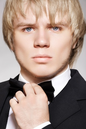 Close-up portrait of young fashion man in evening gentleman style with bow-tie and black suit  photo
