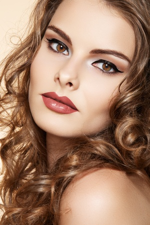 Beautiful woman with fashion make-up and shiny curly hair. Elegant hairstyle for long hair  Stock Photo