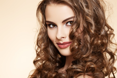 Lovely model with shiny volume curly hair. Pin-up style on beige background  photo