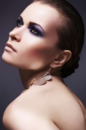 look up: Beautiful woman model with dark evening purple smoky eyes make-up, slicked hairstyle, shiny accessories on violet background