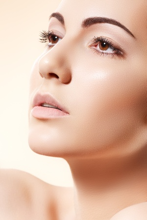 Spa, beauty, skincare, wellness & health. Glamour close-up portrait of beautiful woman model face with purity healthy skin & light make-up on bright beige background  photo