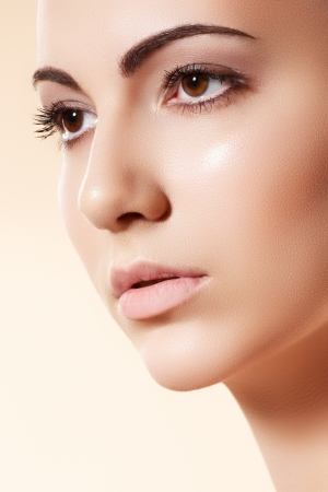 Spa, skincare, wellness & health. Close-up portrait of beautiful female model face with purity health skin & light make-up on bright beige background  Stock Photo