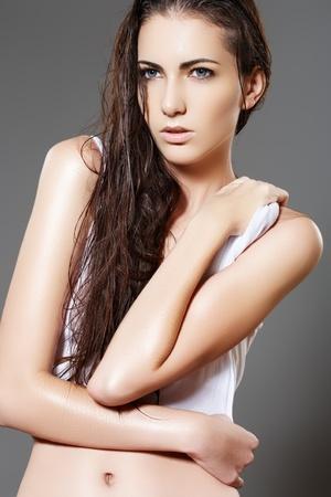 Beautiful fashion slim wet woman model in white blank t-shirt on gray background Stock Photo - 11572496