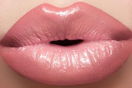 Gentle kiss. Beautiful fashion lip make-up. Macro of female lips with natural light makeup