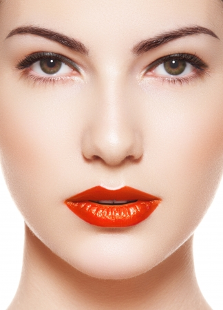 Cute model face with bright evening make-up, orange lipstick, purity skin on white background  Foto de archivo