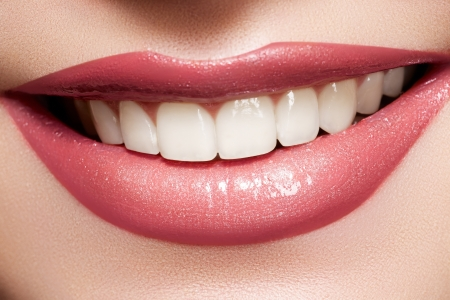 smile close up: Close-up happy female smile with healthy white teeth, bright gloss lips make-up. Cosmetology, dental and beauty care  Stock Photo