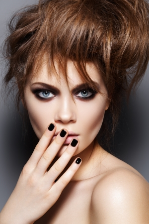 Fashion model with tousled hair, make-up, manicure. Portrait of young fashion woman with punk rock hairstyle, dark make-up, black nail polish  photo