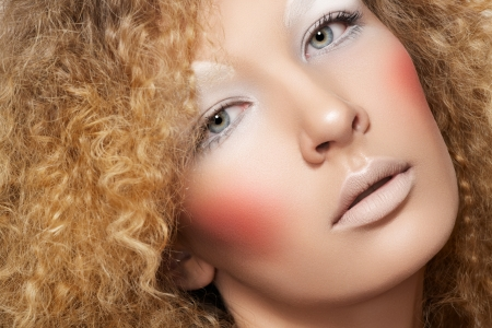 Lovely model with shiny volume curly hair, winter white eyeshadows make-up, pale lips and pink cheeks  Christmas look with frizzy hairstyle  photo