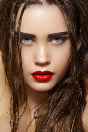 Hot young woman model with sexy bright red lips makeup, strong eyebrows, clean shiny skin and wet hairstyle  Beautiful fashion portrait of glamour female face  Foto de archivo