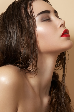 Hot young woman model with sexy bright red lips makeup, strong eyebrows, clean shiny skin and wet hairstyle  Beautiful fashion portrait of glamour female face  photo