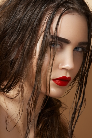 Hot young woman model with sexy bright red lips makeup, strong eyebrows, clean shiny skin and wet hairstyle  Beautiful fashion portrait of glamour female face Stock Photo - 14069263
