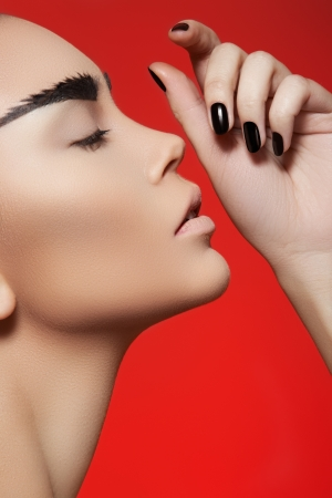 Fashion style, manicure, cosmetics and make-up  Profile portrait of beautiful woman with creative strong eyebrows makeup, clean skin, cheekbones and dark manicure on bright red background  Stock Photo - 14063390