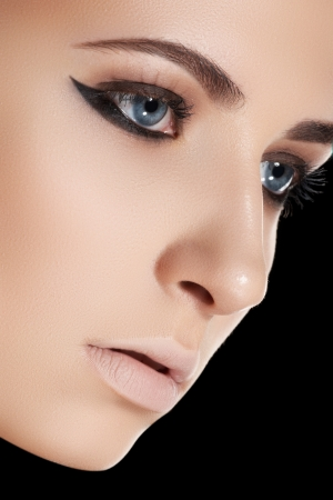 Beauty, cosmetics and fashion  Beautiful woman model face with clean skin, liner eye makeup, pale lips make-up on black background  Foto de archivo