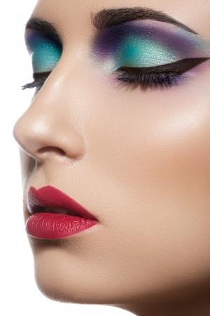 Closeup beauty portrait of attractive model face with bright visage  Multicolored eye makeup and vinous lips make-up  Foto de archivo