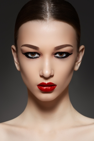 Sexy woman model with face bright red lips makeup, strong eyebrows   cheekbones, fashion eyeliner make-up and healthy clean skin  Evening glamour style
