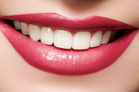 Close-up happy female smile with healthy white teeth, bright magenta lips make-up  Cosmetology, dentistry and beauty care  Macro of woman s smiling mouth