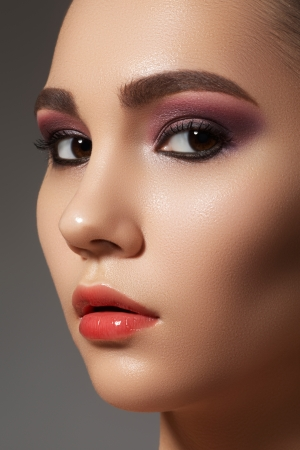 Closeup beauty portrait of attractive model face with bright visage  Purple eye makeup and gloss lips make-up  Stock Photo