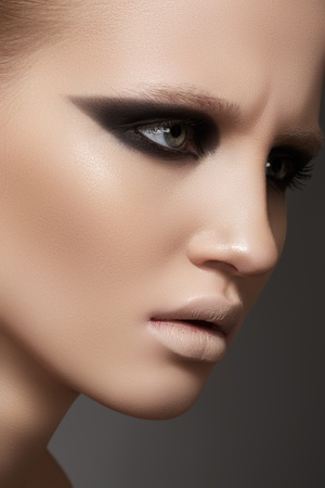 Beauty close-up portrait of beautiful sexy woman model with dark evening catwalk fashion eyes make-up and pale lips on gray background  photo