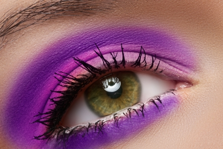 Cosmetics and beauty care  Macro close-up of beautiful green female eye with bright fashion runway make-up  Violet eyeshadows and black eyeliner  photo