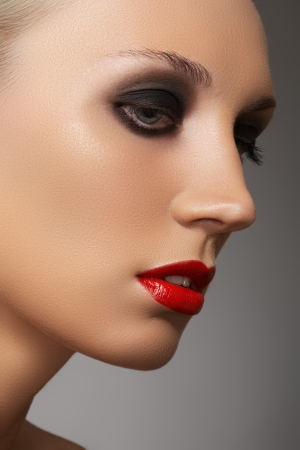 Closeup beauty portrait of attractive model face with fashion visage  Dark smoky eye makeup and bright red lips make-up  photo